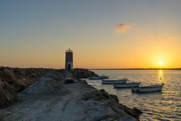 Kleiner Leuchtturm auf Djerba mit Fischerbooten